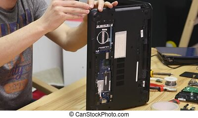 Male engineer disassembles a laptop with a screwdriver....