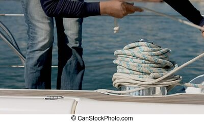 Hands wrapping a rope around a winch on a boat - Handheld...