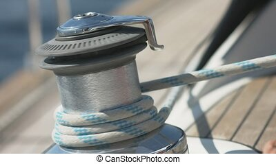 Man pulling ropes, winding sheets around winches - Sailing,...
