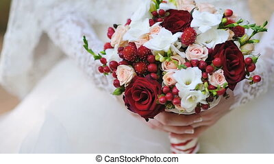 bride is holding a beautiful wedding bouquet.