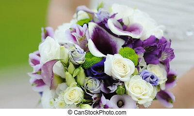 bride is holding a beautiful wedding bouquet