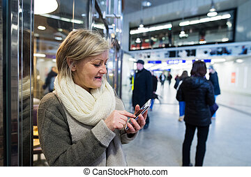 Senior woman with smartphone in hallway of subway -...
