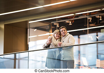 Senior couple standing at the train station, waiting, hugging