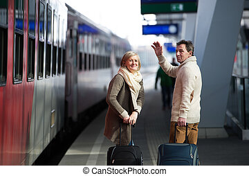 Senior couple on train station pulling trolley luggage,...