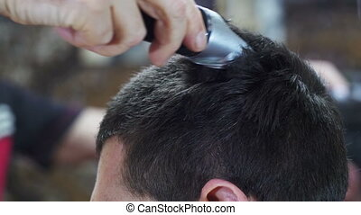 Hairdresser Cuts the Hair of a Young Man with Clipper at...