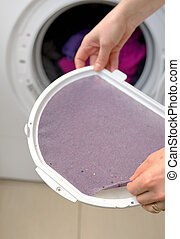 Taking the lent of Dryer Machine - Woman Taking the lent of...