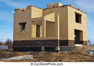 Individual house of yellow brick under construction