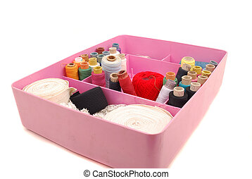 Small items for sewing in a box on a white background