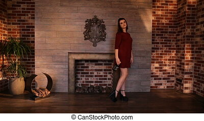 A girl in a burgundy dress on a background of fire - The...