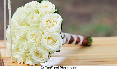 Beautiful bouquet of white roses lies on a swing in the...