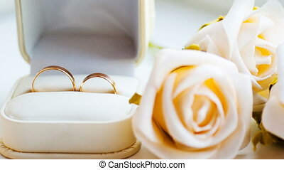 Two gold rings and white roses on the table of the wedding...
