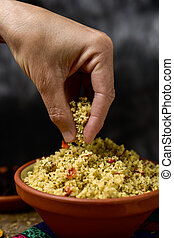 young man eating tabbouleh with his hand - closeup of a...