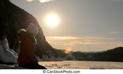Girl sits on the shore of a frozen lake at sunset.