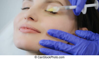Woman receive botox injection in lips - Doctor making botox...
