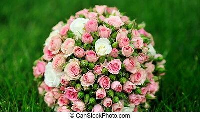 Wedding bouquet of pink roses lies on green grass.