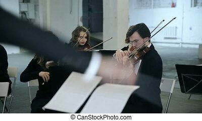 Violinists and conductor playing music.