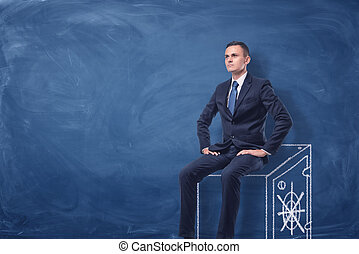 Businessman on blue chalkboard background sitting on a strongbox drawn in white.