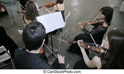 Four violinists playing music in hall.