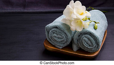 Spa relaxing setting with towels and flowers