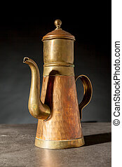 an copper coffeepot - an old copper coffeepot on a black...