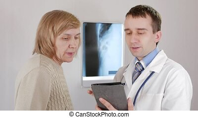 A young male doctor shows the results of tests on a tablet computer. The patient is a woman aged.