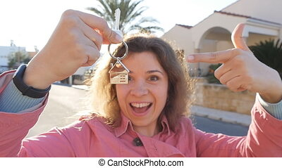 Happy woman with keys at home. Real estate concept