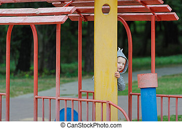 Little boy peeping on the children's playground