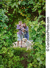 Family of three with a dog in the park, mother and father holding a child