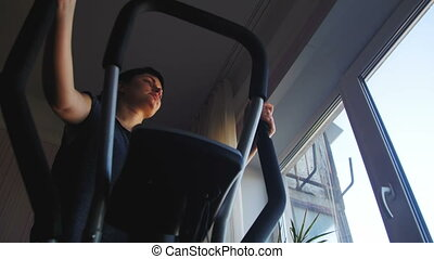 Young Woman Exercising on Elliptical Machine at Home on...