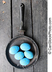 Easter eggs in a frying pan on a vintage wooden background -...