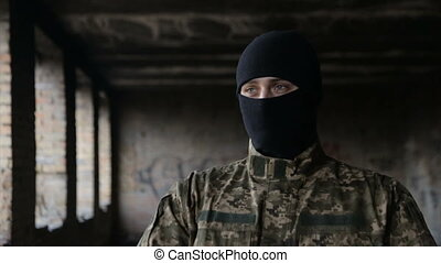 A man in camouflage and a black mask on an old abandoned...