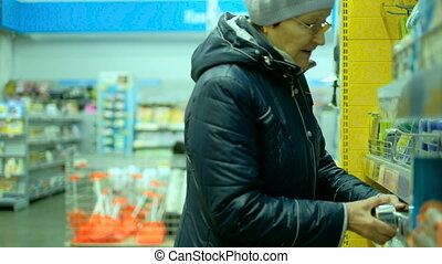 Elderly woman choosing produce in supermarket . grandmother...