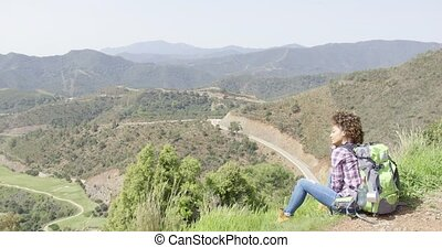 Delightful young female backpacker - Back view of young...