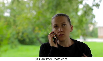 Confident young businesswoman speaks on the phone in green park