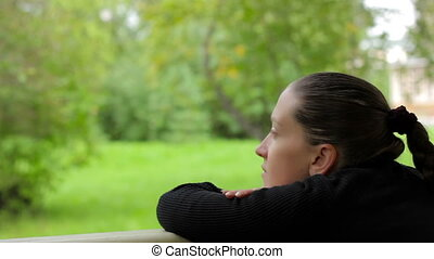 Pensive thoughtful girl meditates on the background of green...