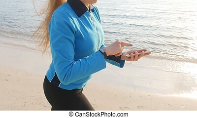 Woman looking at fitness tracker - Fitness woman looking at...