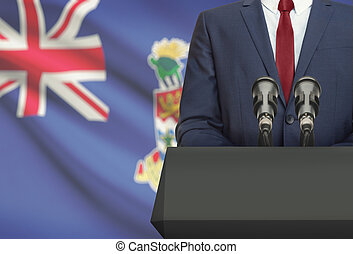 Businessman or politician making speech from behind a pulpit with national flag on background - Cayman Islands