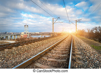 Railroad at sunset. Railway station against blue cloudy sky