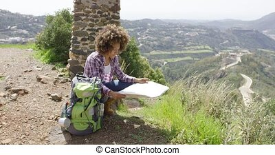Young female sitting with backpack and map - Young female...