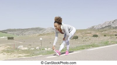 Fit woman in sportive clothing stretching body - Young woman...