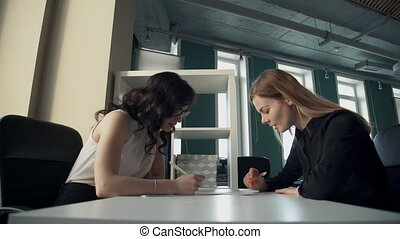 Two business women in office discuss topics, watching documents