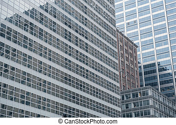Different constructions mirroring in tall buildings - Close...