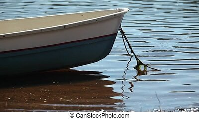 Rowing boat moored at shore Swaying on the wave, summer...