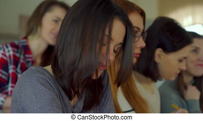 Female student touches her hair at the lecture hall