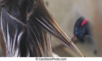 Professional Hairdresser Bleaching Girl's Hair.