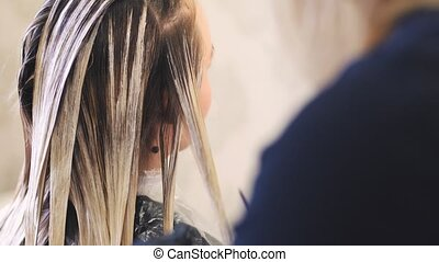 Stylist hairdresser makes hair coloring, blonding. She uses...