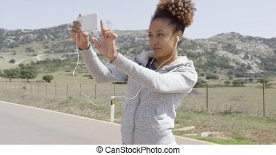 Young woman taking picture of nature - Young woman in...