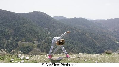 Sportive woman stretching on nature - Young fit woman...