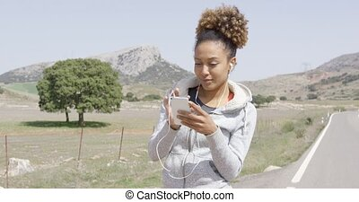 Pretty young sportive woman with phone