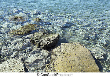 Close up view of crystal clear turqouise water with rocky -...